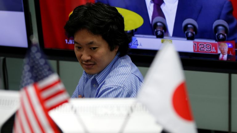 Employee of a foreign exchange trading company in Tokyo looks at a monitor on US election night 9 November 2016.