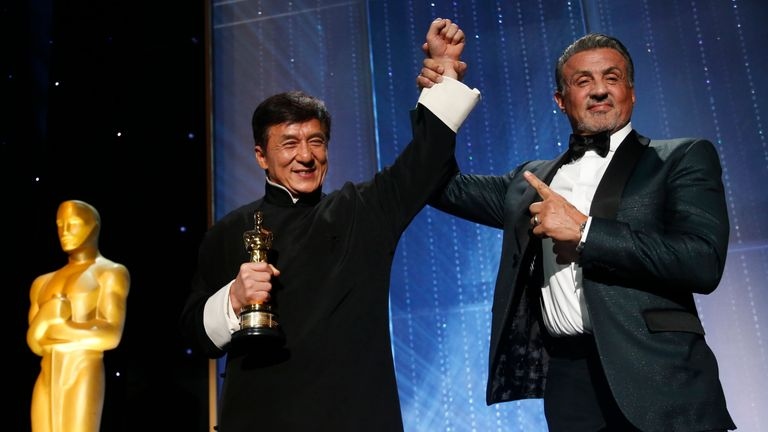 Actor Jackie Chan is congratulated by fellow actor Sylvester Stallone