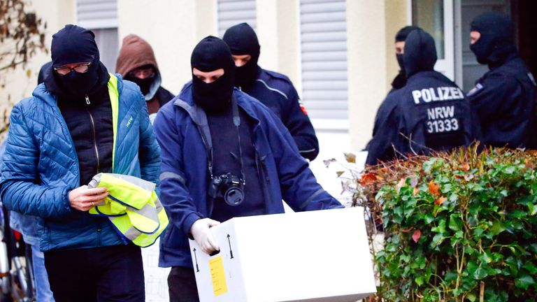 Police in Bonn take away crates of documents from an apartment