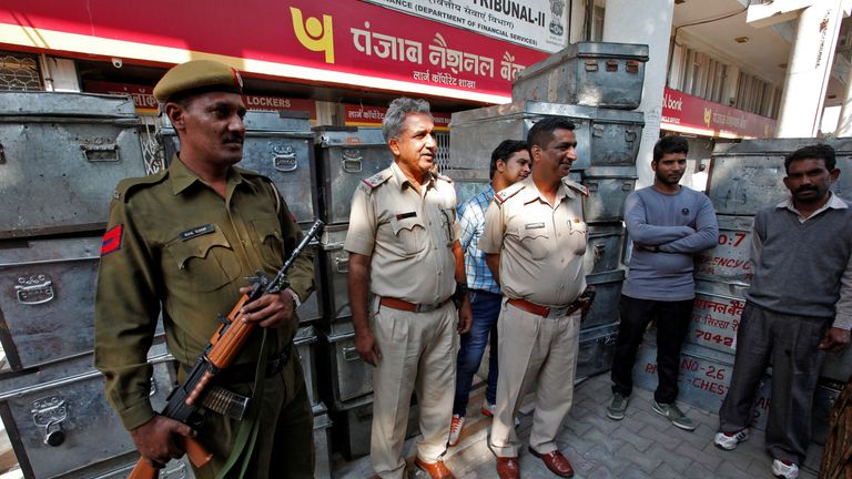 Policemen stand guard outside a bank in Chandigarh