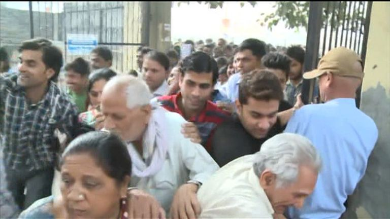 Indians surge through the gates of a bank's entrance in New Delhi