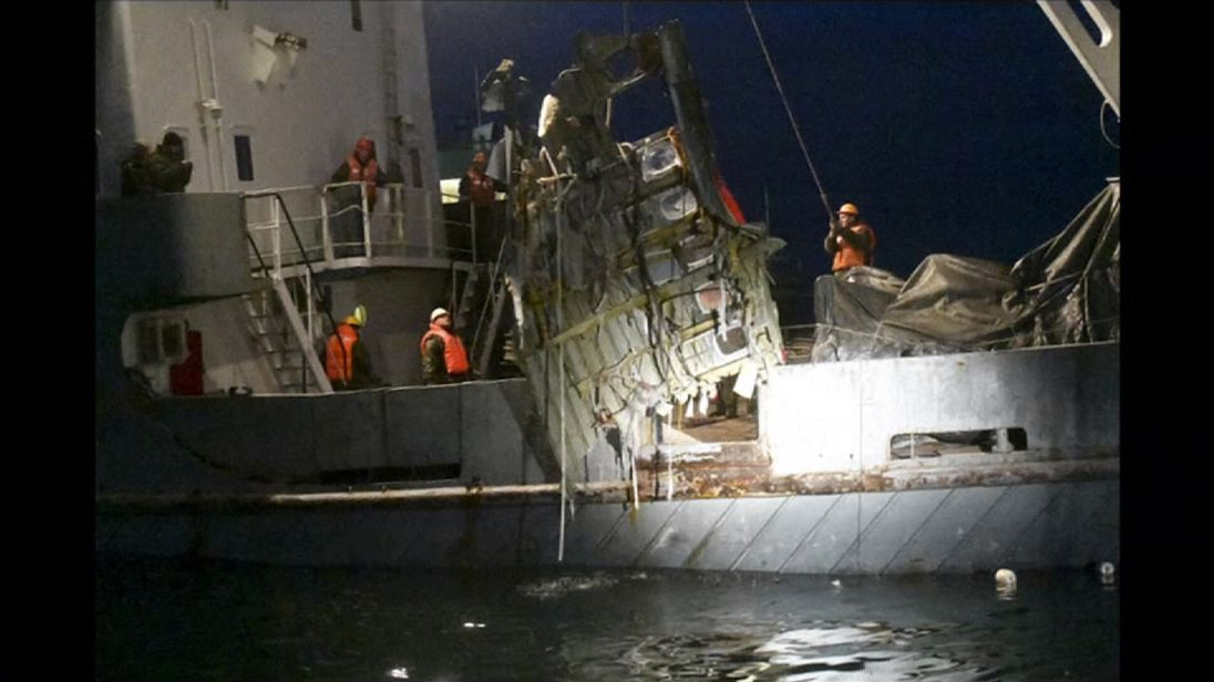 Rescue workers lift a piece of fuselage out of the water