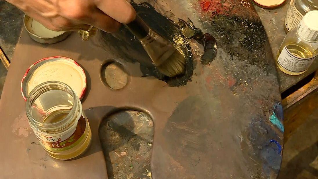 An artist mixes black paint on a palette.