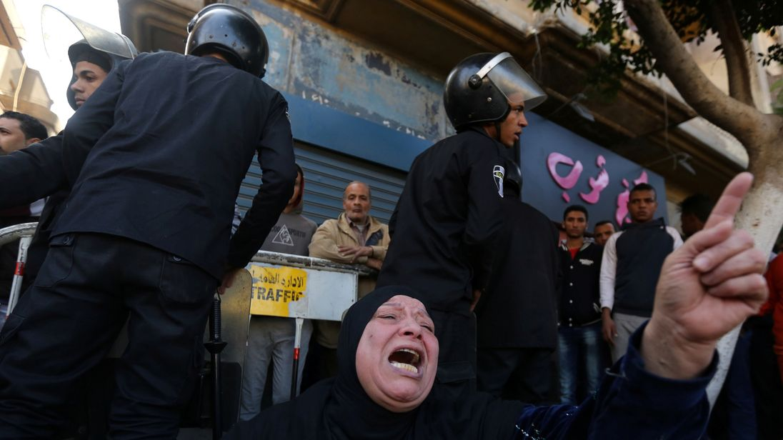 A woman cries while sitting in front of police officers in front of  the cathedral in Cairo after the bomb blast