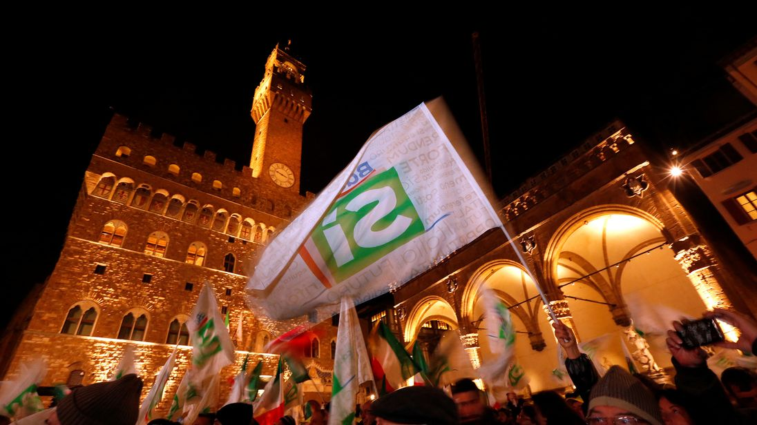 "Supporters wave flags as Italian Prime Minister Matteo Renzi speaks during the last rally for a ""Yes"" vote"