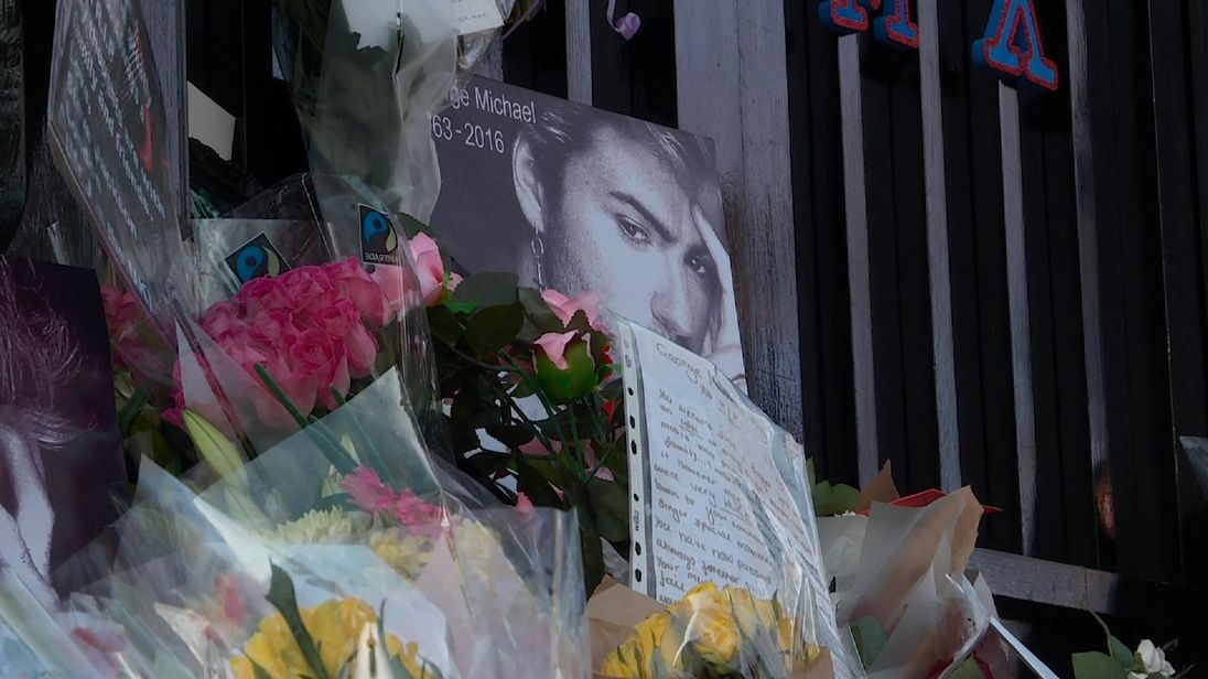Floral tributes, notes and photographs at the gates of George Michael's London home