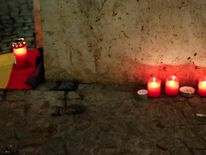 Candles are left close to the scene where at least 12 people died as a lorry crashed into a Christmas market