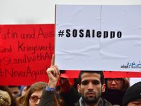 A person holds a banner during a demonstration for peace in Syria and against bombings on Aleppo in front of the Reichstag building which houses Germany's Bundestag lower house of parliament, on December 17, 2016 in Berlin
