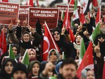 Protesters shout slogans and hold placards reading 'Aleppo can not be left under bombardment' during a demonstration in Reyhanli in Hatay near the Syrian border on December 17, 2016. Thousands of trapped civilians and rebels waited desperately for evacuations to resume from the last opposition-held areas of Aleppo after the operation was suspended by the Syrian regime