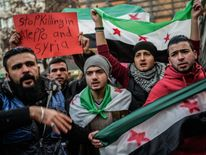 Syrians living in Turkey hold Syrian opposition flags during a protest against the Syrian regime along Istiklal Avenue in Istanbul on December 17, 2016. Thousands of trapped civilians and rebels waited desperately for evacuations to resume from the last opposition-held areas of Aleppo after the operation was suspended by the Syrian regime