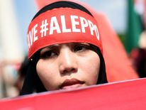 A Malaysian Muslim woman holds a placard during a demonstration in solidarity with the inhabitants of the embattled Syrian city of Aleppo, outside the Russian Embassy in Kuala Lumpur on December 16 , 2016. Russia announced it was negotiating with the Syrian opposition and seeking a nationwide ceasefire, as the evacuation of civilians and fighters from the last rebel-held parts of Aleppo entered a second day