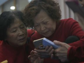 Chinese grandmothers play on their smartphones