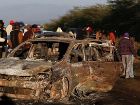 People look at wreckages of burnt out cars engulfed by the fireball