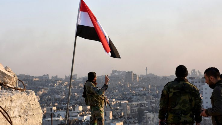 A Syrian government soldier gestures under the national flag in eastern Aleppo
