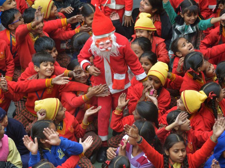 A boy dressed as Santa is mobbed by his classmates as he gives out sweets in Amritsar, India