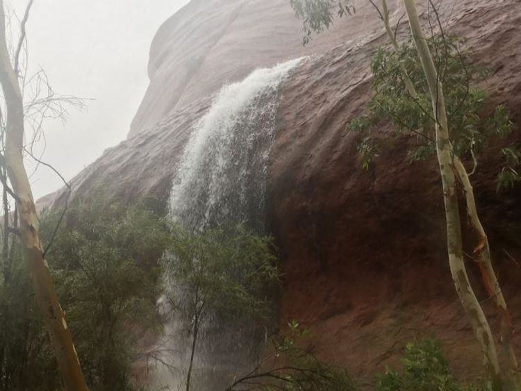 Water runs off Uluru. Pic: @BiancaH80 and @waginski