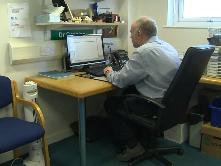 A GP types in his office.