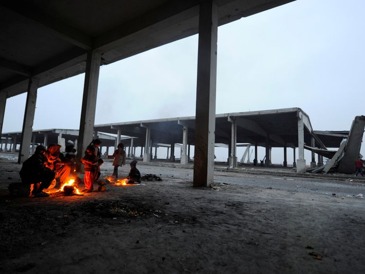 Syrians evacuated from eastern Aleppo keep warm by a fire, under a shelter in government controlled Jibreen area in Aleppo, Syria November 30, 2016. REUTERS/Omar Sanadiki