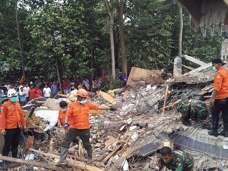 Rescue workers try to find people trapped under rubble
