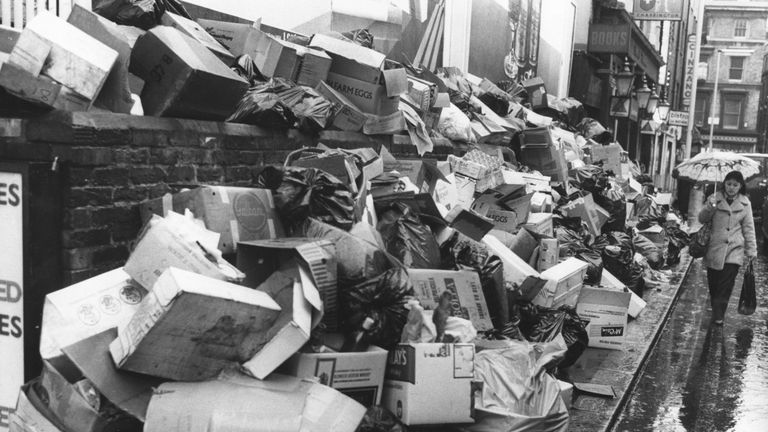 A woman walks past a pavement piled high with rubbish due to a refuse collector's strike in 1979