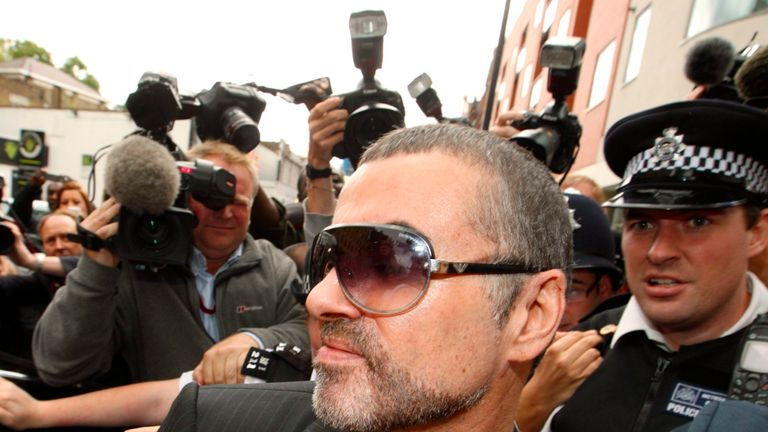 British singer George Michael is escorted out of Highbury Corner Magistrates Court in London in 2010 after pleading guilty to driving under the influence of drugs and possessing cannabis