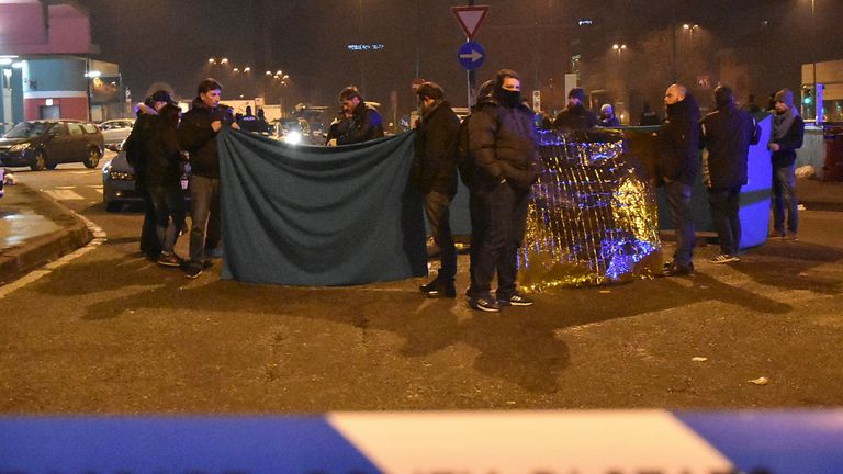 Police officers cover the body of Amis Amri in Milan