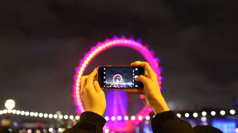 A lucky ticketholder for London's sold-out New Year show takes a photo of the London Eye