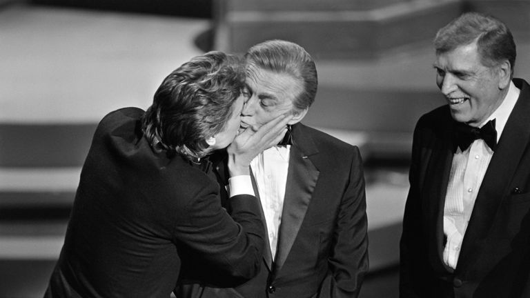 Acotr Michael Douglas kisses his father Kirk at the 1985 Oscars