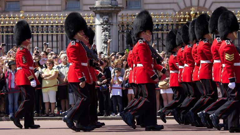 Guardsmen march past onlookers into Buckingham Palace during the Changing of the Guard in London on July 23, 2012, four days before the start of the London 2012 Olympic Games.