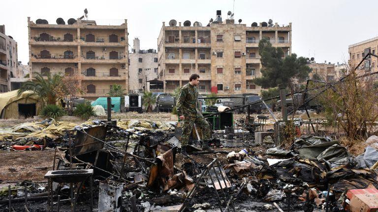 A Russian soldier inspects the damage at a field hospital that was reportedly destroyed by rebel shelling in Aleppo