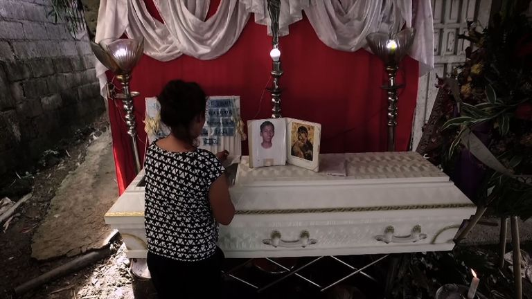A grieving woman watches over the coffin of her 31-year-old brother, a victim of the Philippines' war on drugs.