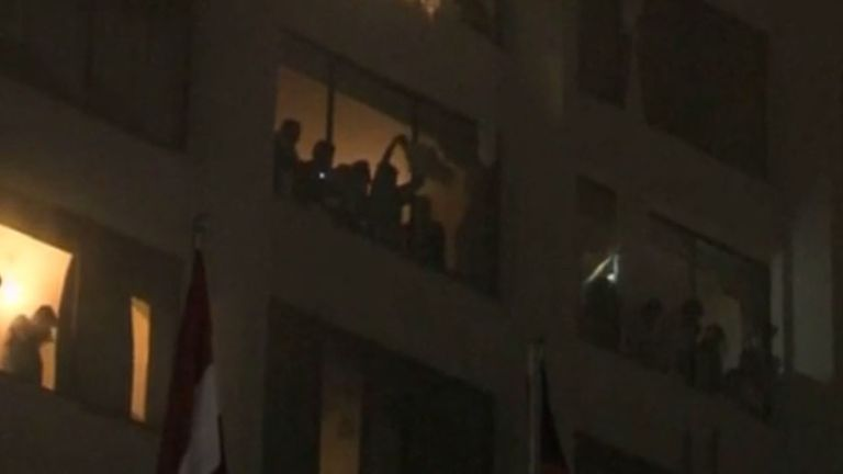People staying at the burning Regent Plaza in Karachi wave from windows. Pic: Express Tribune