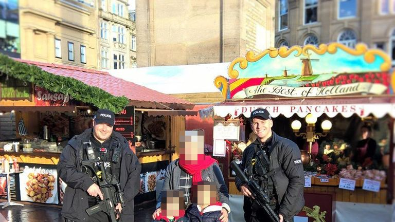 The armed officers posed with shoppers at the market
