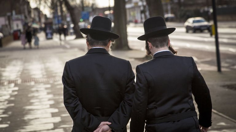 Jewish men walk along the street in the Stamford Hill area of London