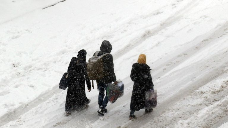 Syrians walk in a snow covered street in the town of Maaret al-Numan, in Syria's northern province of Idlib, near Aleppo, on December 21, 2016