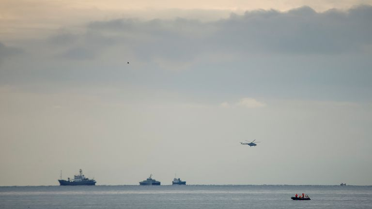 A helicopter and ships at the crash site in the Black Sea
