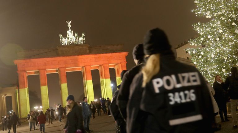 The Brandenburg Gate is illuminated as police walk past the day after a truck drove into a crowded Christmas market
