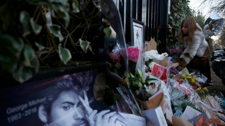 A woman lays flowers outside the home of George Michael in London