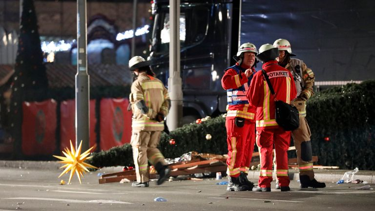 Firefighters discuss what action is needed at the site when a bus crashed into a Christmas market