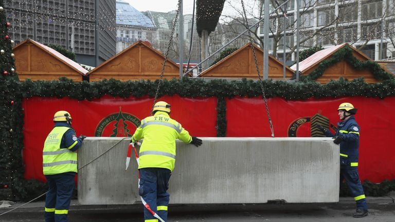 Workers install concrete blocks as a security barrier on the periphery of the reopened Breitscheidplatz Christmas market in Berlin following lorry attack
