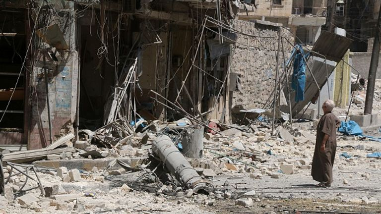 A Tariq al-Bab resident inspects damage caused by an airstrike in August