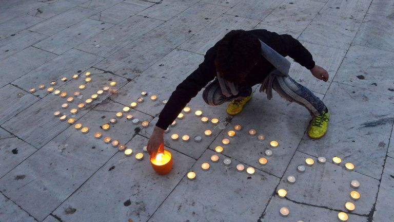 A Syrian boy lights candles and write the word 'Aleppo' during a demonstration in support of the inhabitants of the embattled Syrian city of Aleppo, in Thessaloniki, on December 16, 2016
