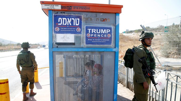 Israeli soldiers are seen next to a bus stop covered with posters from the Israeli branch of the U.S. Republican party campaign in favour of Donald Trump, near the West Bank Jewish settlement of Ariel October 6, 2016
