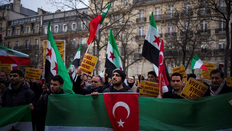 Syrian demonstrators protest near the Iranian Embassy against Iranian involvement in the siege of Aleppo, on December 17, 2016 in Paris, the latest in a series of demonstrations in Europe over the Syria crisis. Protests have been staged in several European cities as the horror in Aleppo has unfolded, with reports of atrocities including summary executions