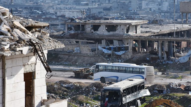 A bus drives through the government-controlled crossing of Ramoussa, on the southern outskirts of Aleppo, on December 18, 2016, during an evacuation operation of rebel fighters and civilians from rebel-held areas