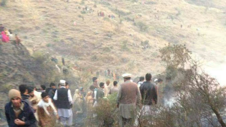 Villagers look on as debris from the plane is found in in the Havelian area