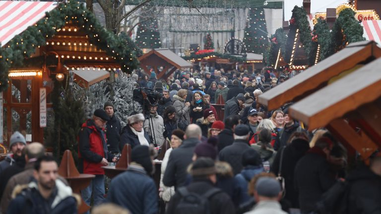 Visitors walk through the reopened Breitscheidplatz Christmas market only a short distance from where three days ago a truck plowed into the market, killed 12 people and injured dozens in a terrorist attacK
