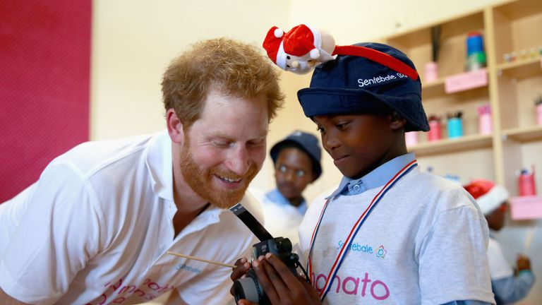 Prince Harry helps a young boy use a Fuji Instax camera during a photography activity at the new Mamohato Children's Centre on November 26, 2015 in Maseru, Lesotho.