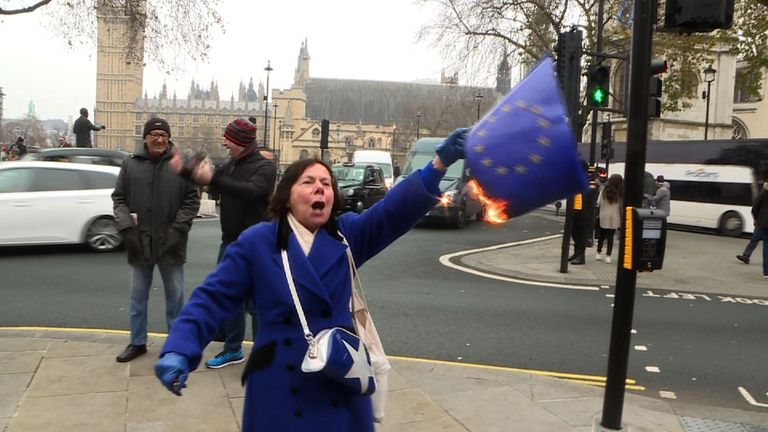 A protester burns an EU flag outside the Supreme Court in London.