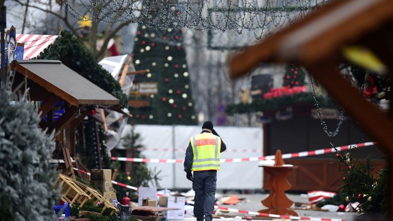 A policeman walks through the damaged Christmas market